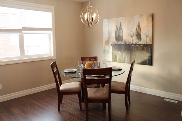 Dining area with a small glass top table and four chairs