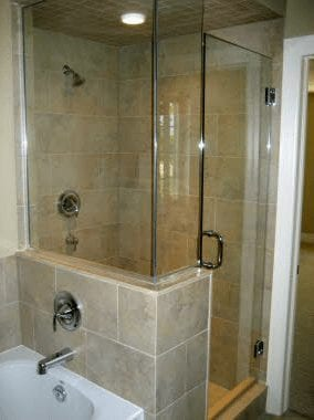 Glass wall shower with bathtub beside it in a bathroom