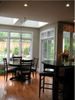 Cozy kitchen with breakfast bar by a dining area with many windows overlooking the back yard