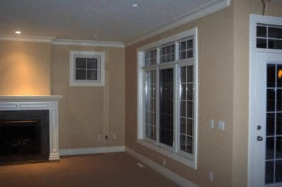 Large panel windows overlooking an empty room with a fireplace