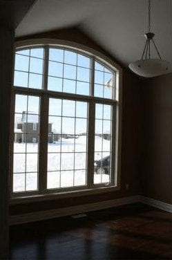 Large paneled window overlooking an empty room