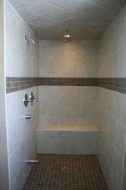 Large walk-in shower with a stone bench