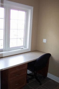 Desk and office chair set up in front of a panel window