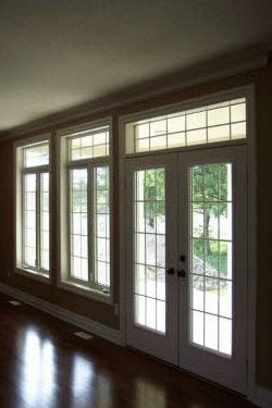 Large panel windows and a window paneled door leading outside