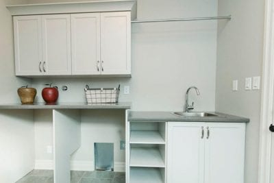 An empty laundry room with sink and space for washer and dryer